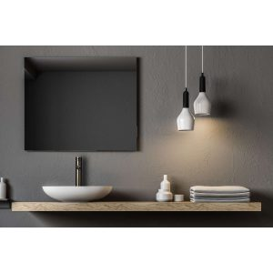 zwarte hoge RVS kraan naast witte wasbak in donkere badkamer